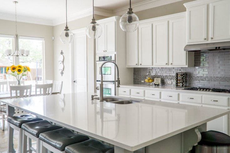 Updated ktichen with white cabinets and grey backsplash