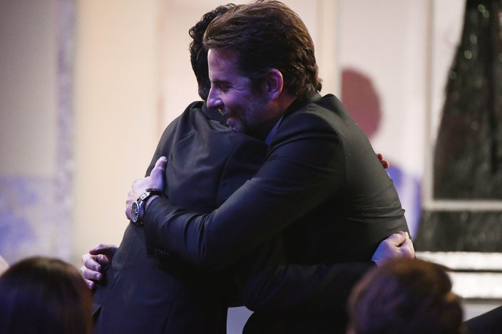 Bradley Cooper and Rami Malek share a hug as Malek walks to the stage to accept his award for best actor