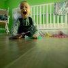 Toddler playing next to crib