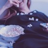 Woman eating popcorn watching tv