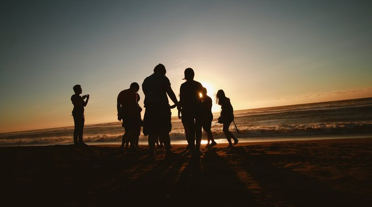 silhouette of friends on beach