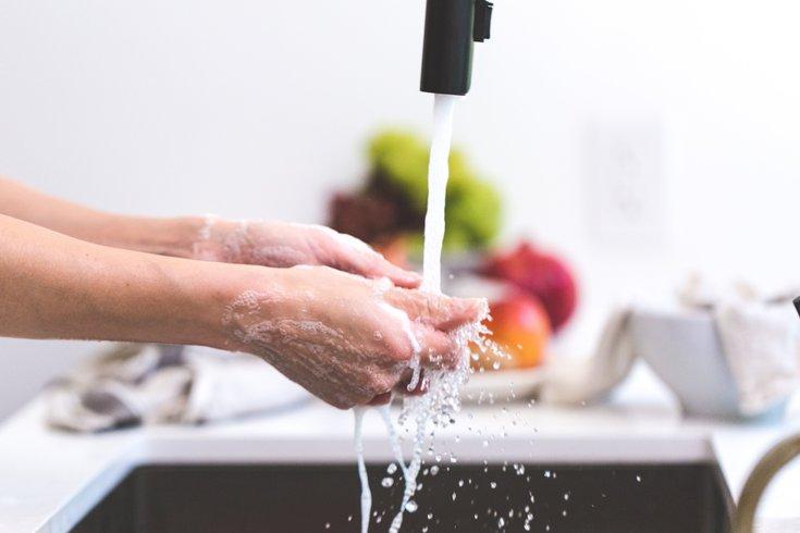 Person washing their hands in kitchen sink