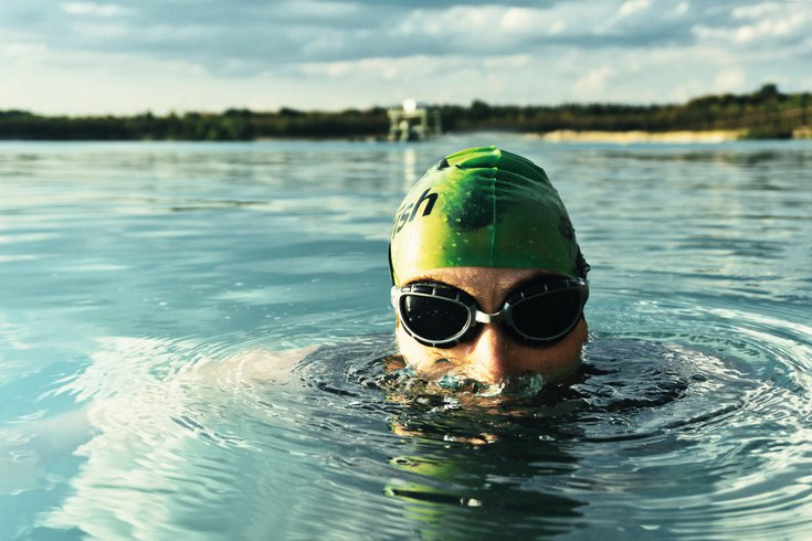 Man swimming in a lake with goggles