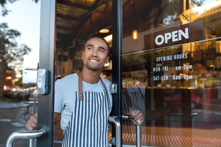 Happy waiter opening on the doors at a cafe