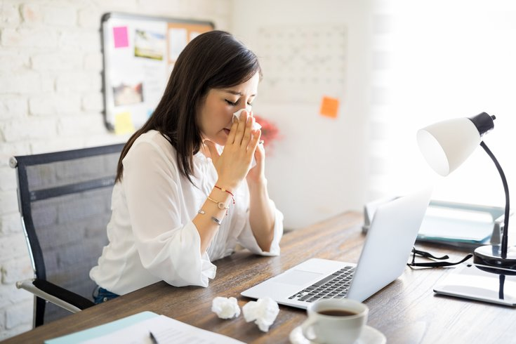 Woman blows nose at desk