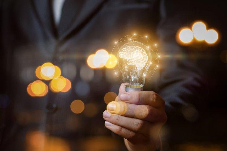 Man holding lightbulb brain power