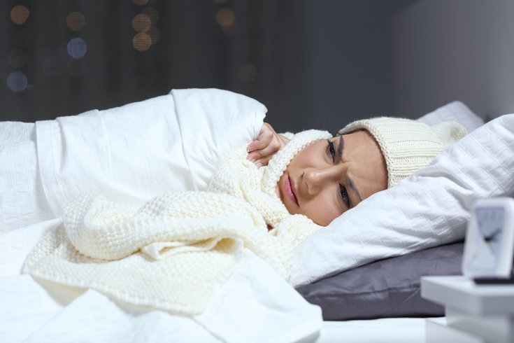 Woman suffering cold in a bed in winter