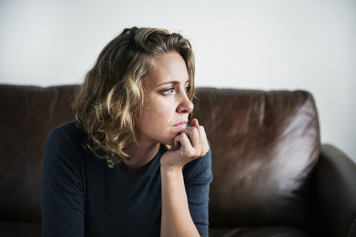 Woman deep in thought on a sofa