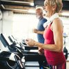 Happy woman running on a treadmill