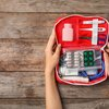 Holding first aid kit on wooden background