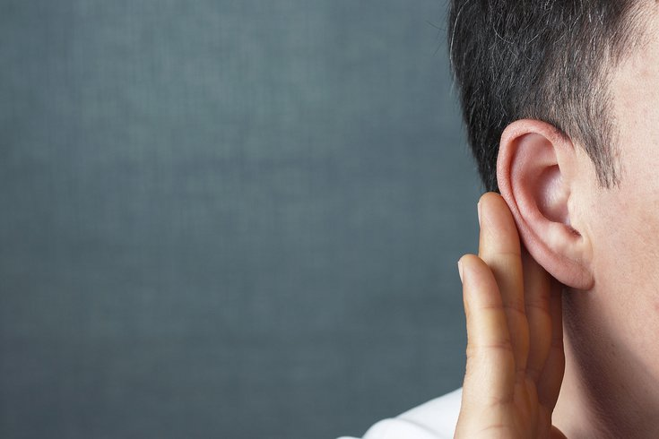 Man listens attentively with palm to ear