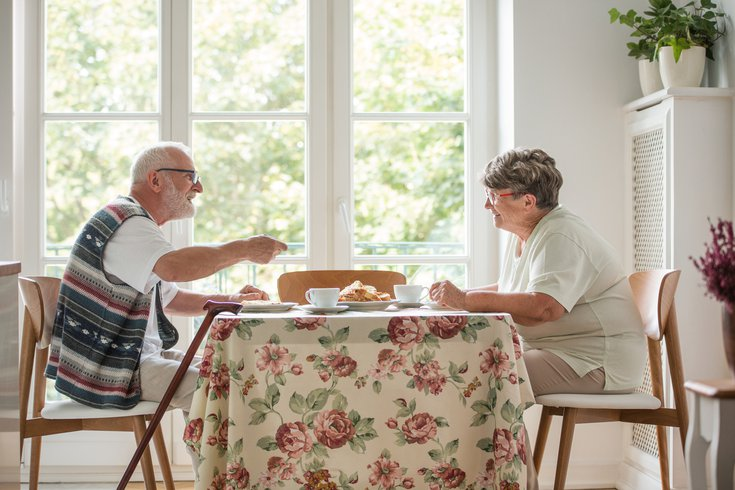 Elderly couple eating a meal at the kitchen table