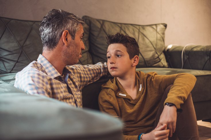 Father talking with teen son in living room
