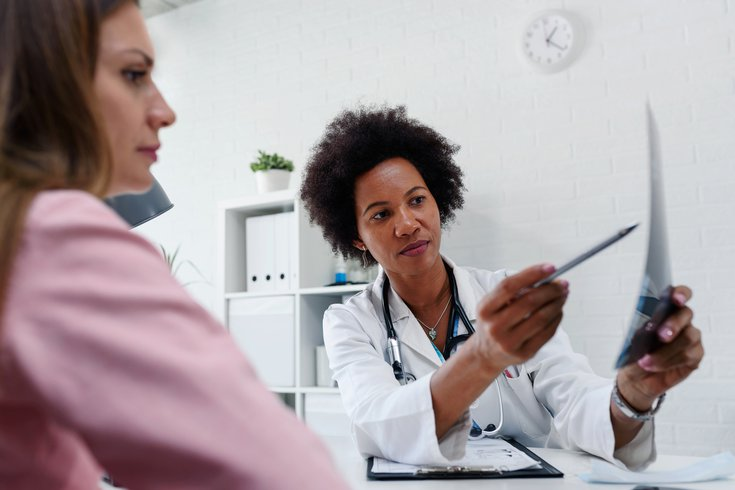 Purchased - Doctor talking with patient at desk in medical office