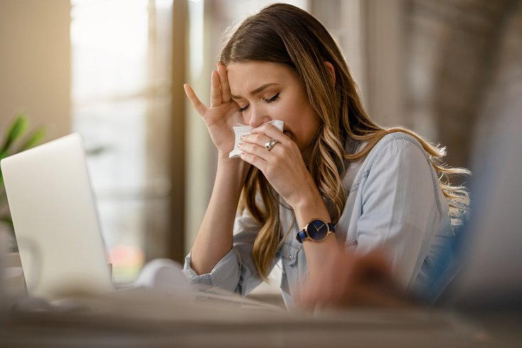 Woman blowing her nose not feeling well