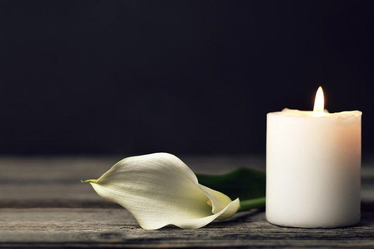 Burning candle and white calla on dark background