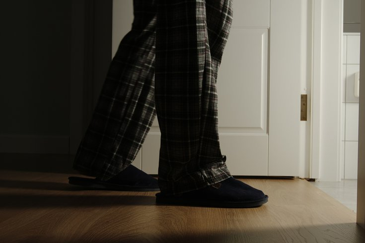 Aged man in a pajamas and slippers walks to a bathroom at home
