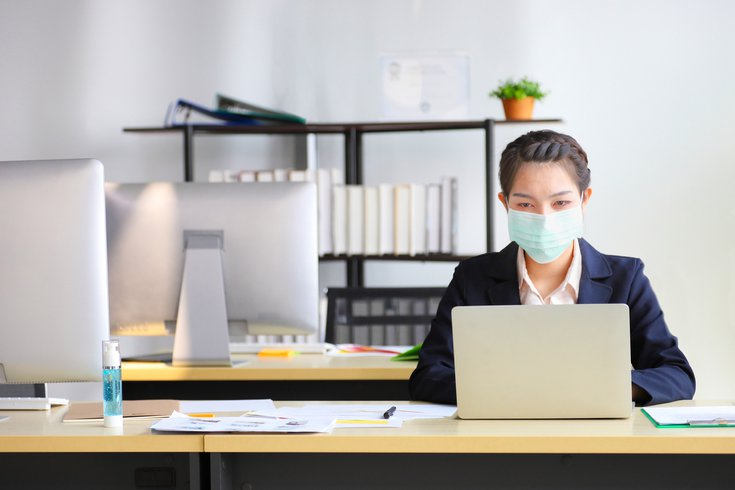 Employee wearing medical face mask while working in the business office