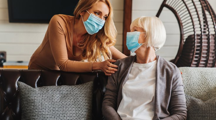 Purchased - Woman interacting with senior citizen in mask