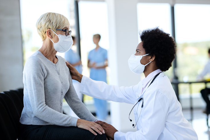 Purchased - Doctor and patient wearing masks while talking
