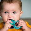 Baby chewing on teething ring stock photo