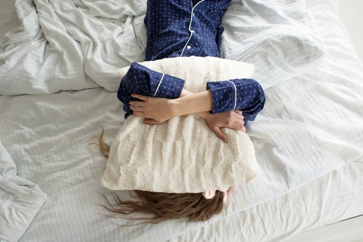 Woman in bed with a pillow over her head