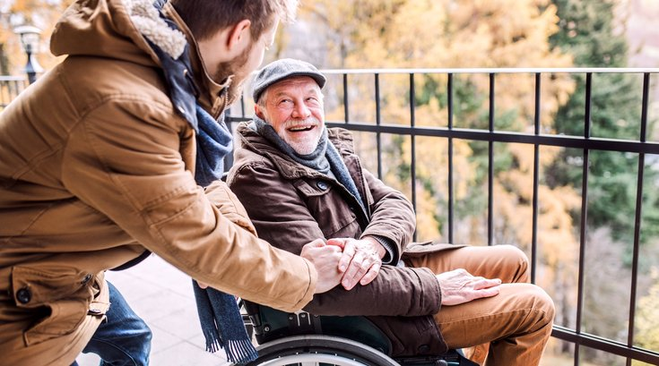 Senior father in wheelchair and young son