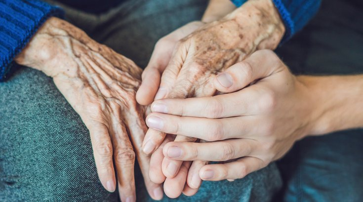 Hands of an old woman and a young man