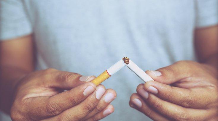 Man refusing cigarette by breaking it in half