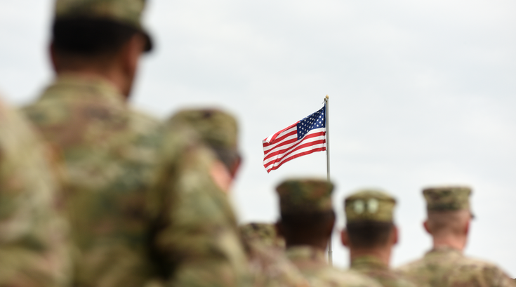 Soldiers in front of flag