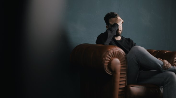 Stressed out man sitting on couch