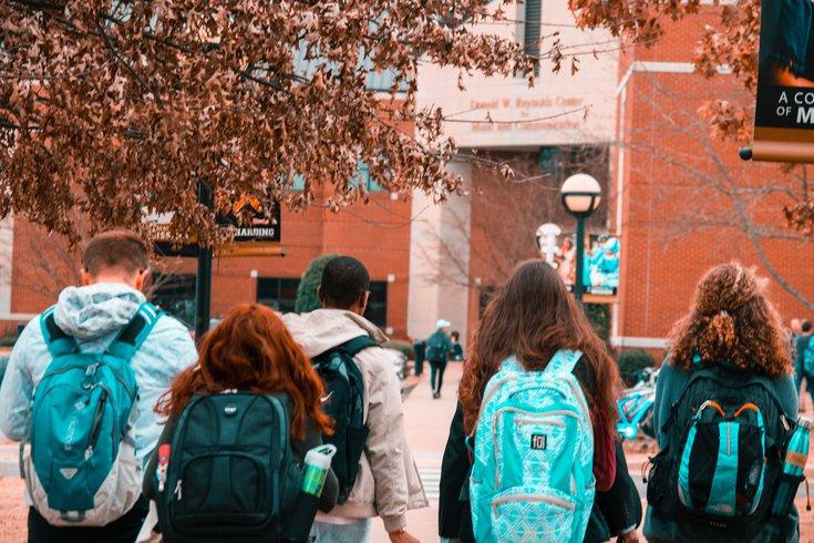 People wearing backpacks on way to school