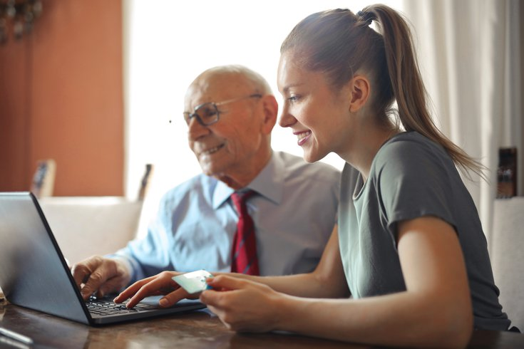 Young woman helping elderly man with finances