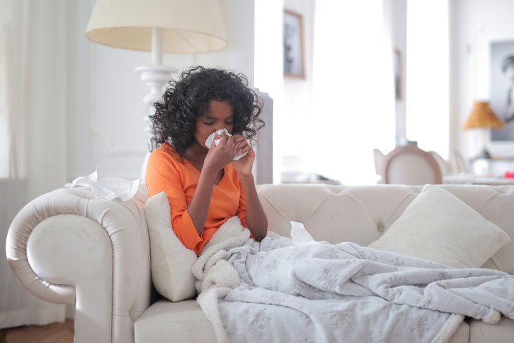 Woman suffering from allergies on her couch