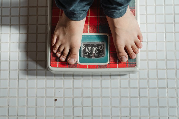 Person standing on a scale on tile floor