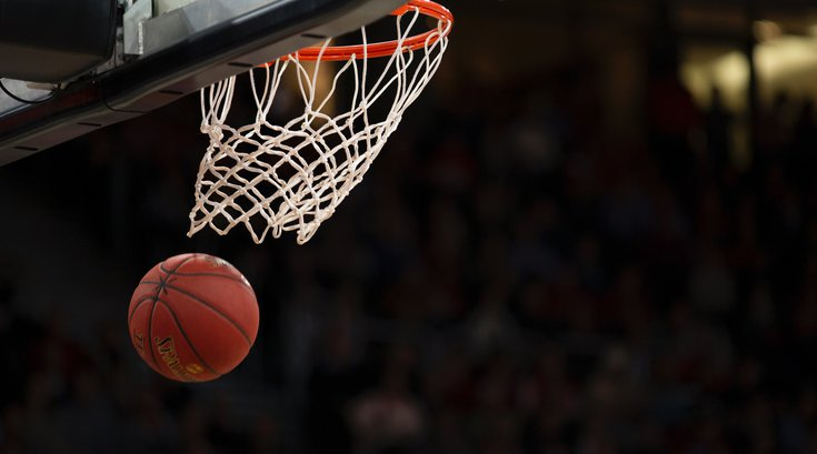Basketball through hoop at stadium