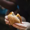Per holding a cheeseburger