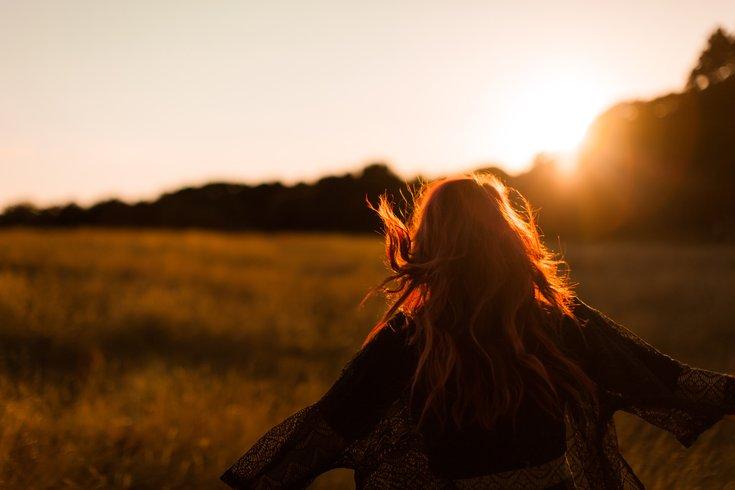 Woman running through field at sunset